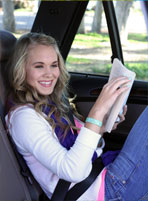 Young girl in moving car reading a book wearing Psi Bands