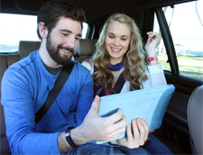 Two people in moving car using tablet wearing Psi Bands